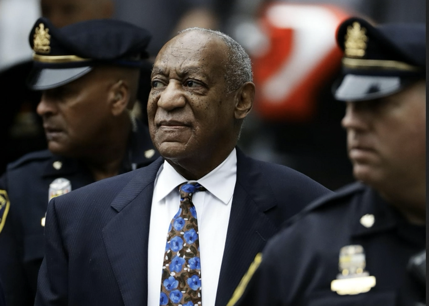 Bill Cosby in a suit looks to his right with police officers next to him